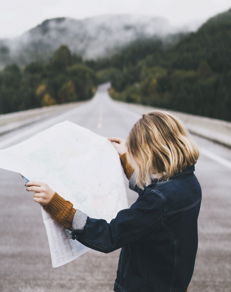 girl-reading-map-with-mountains